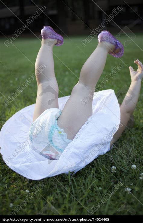 Little girl plays in the grass